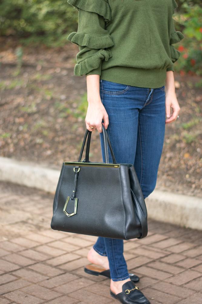 green sweater jeans black handbag