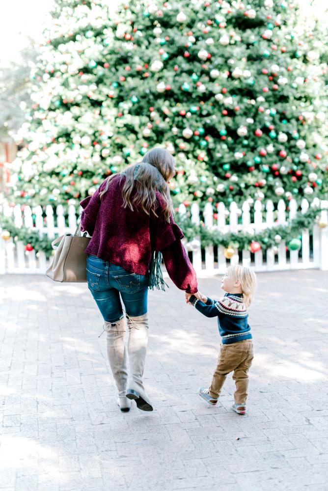 toddler in Chrostmas sweater mom CHristmas tree