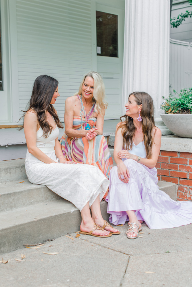 three women chatting on steps of porch