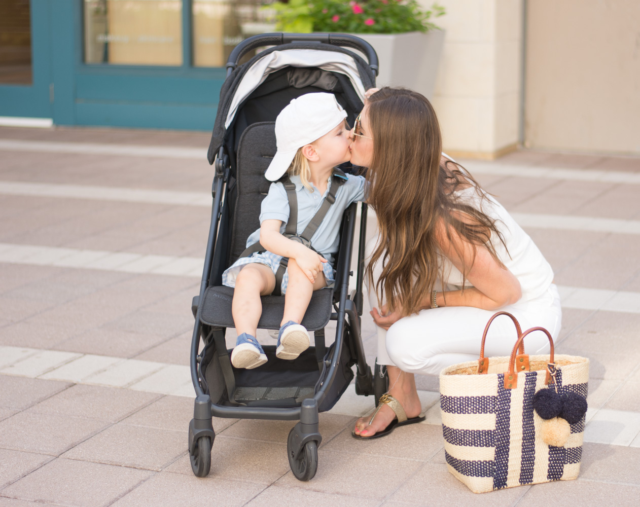 mommy kissing toddler in uppababy muni