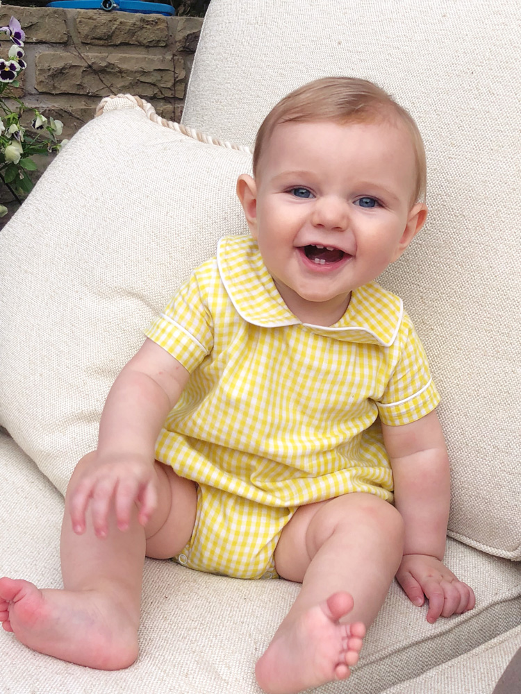 baby boy laughing in yellow sunsuit