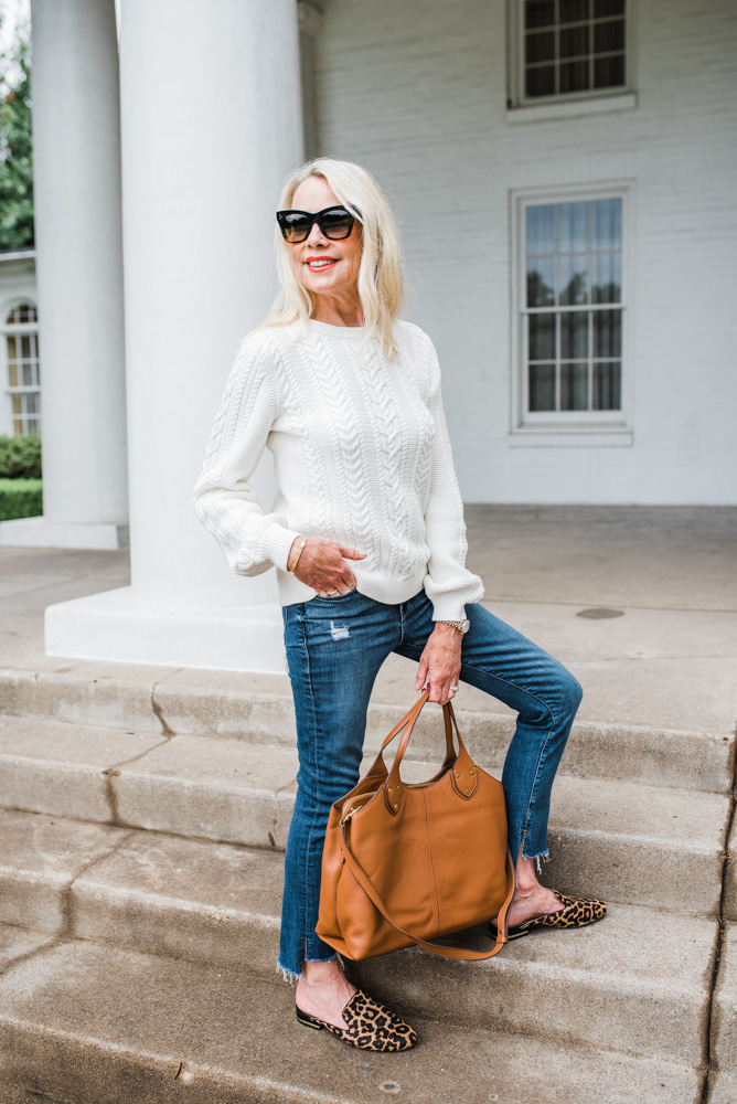 ivory cable knit sweater jeans cognac tote bag