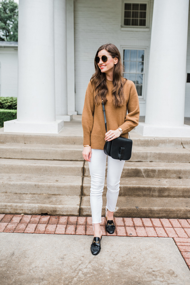 camel sweater white jeans black bag
