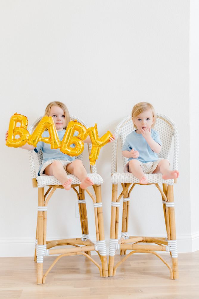 baby announcement two toddlers with baby balloon
