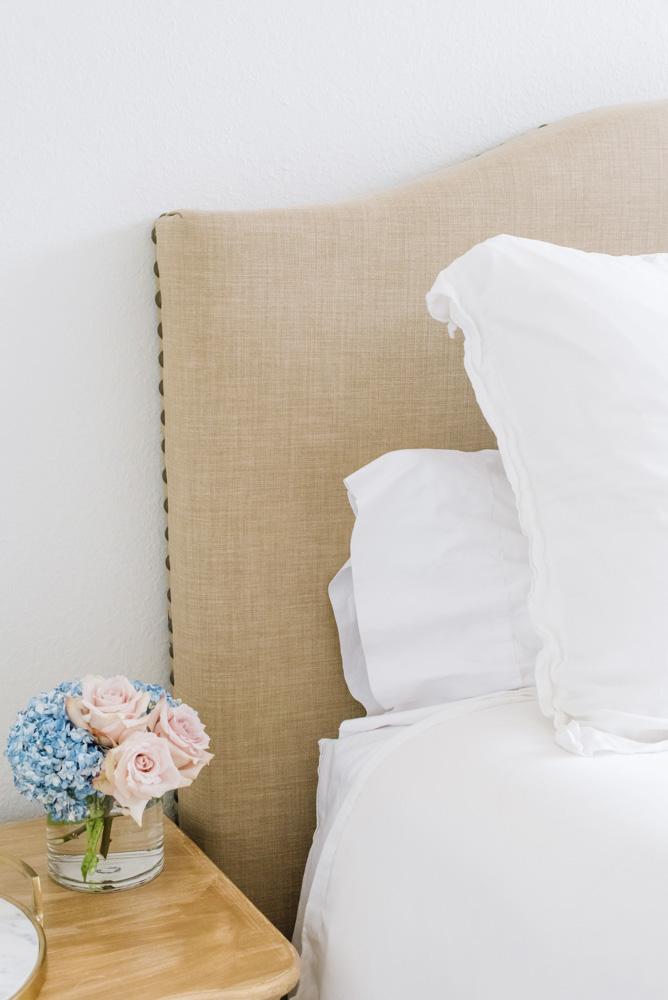 linen headboard white bedding flowers nightstand