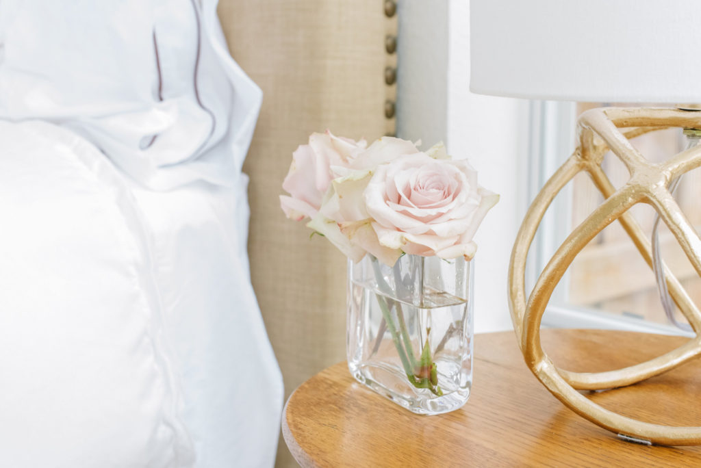gold table lamp pink roses on bedside table