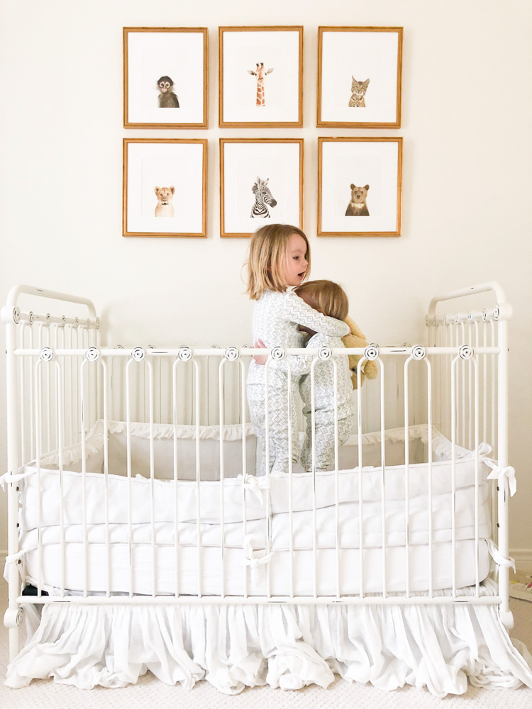 toddler brothers hugging in crib neutral nursery