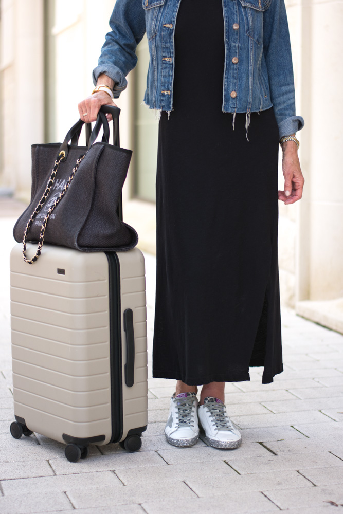woman wearing black maxi dress black tote bag tan suitcase jean jackets