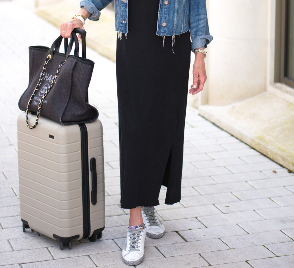black maxi dress golden goose sneakers black tote bag tan suitcase