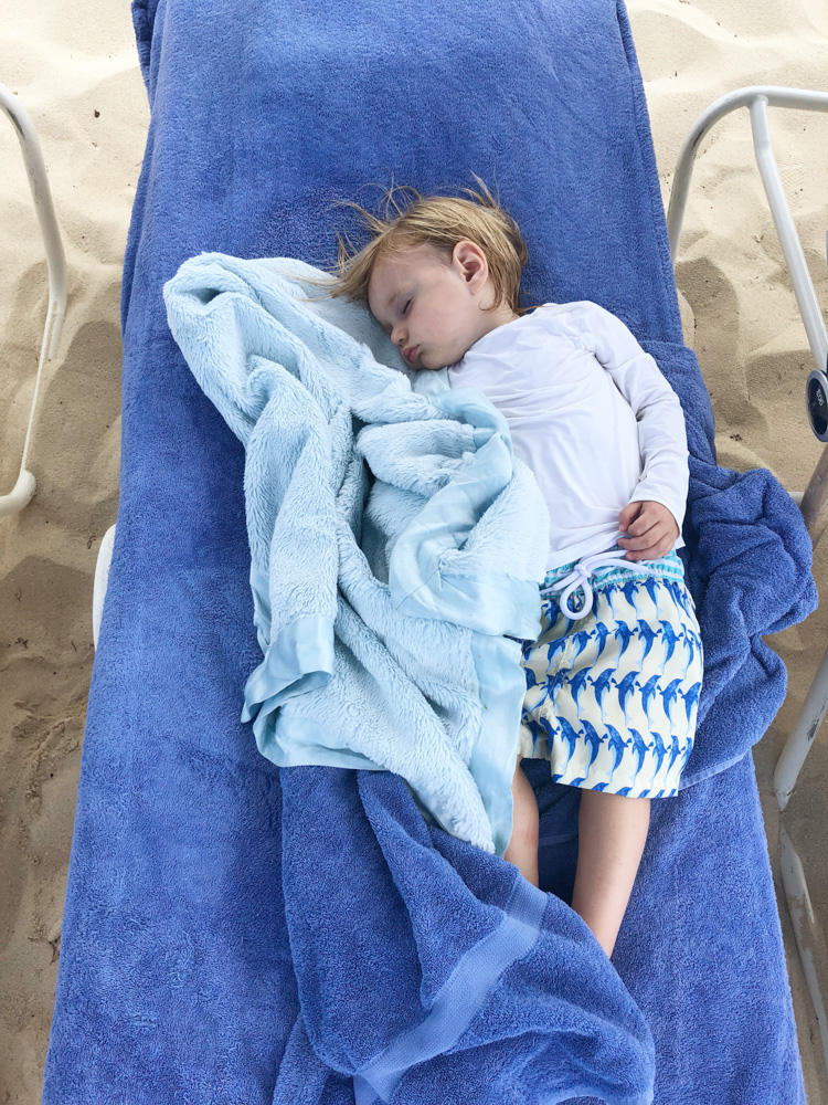 baby boy asleep at the beach