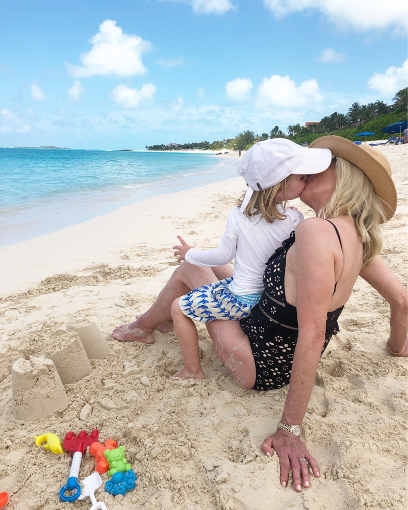 toddler boy kissing grandmother on the beach