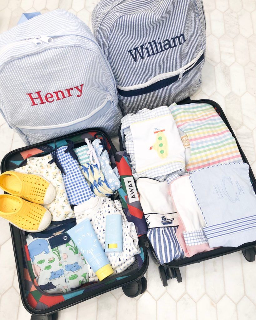 packed suitcase two blu and white striped personalized backpacks