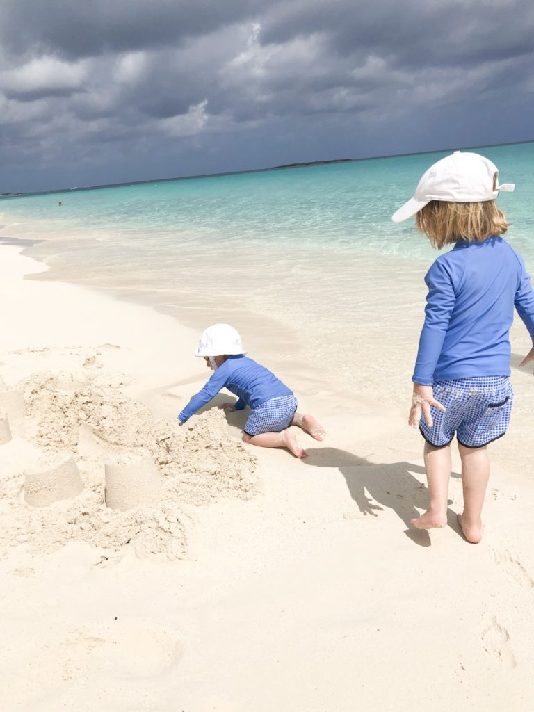 two toddler boys playing on the beach