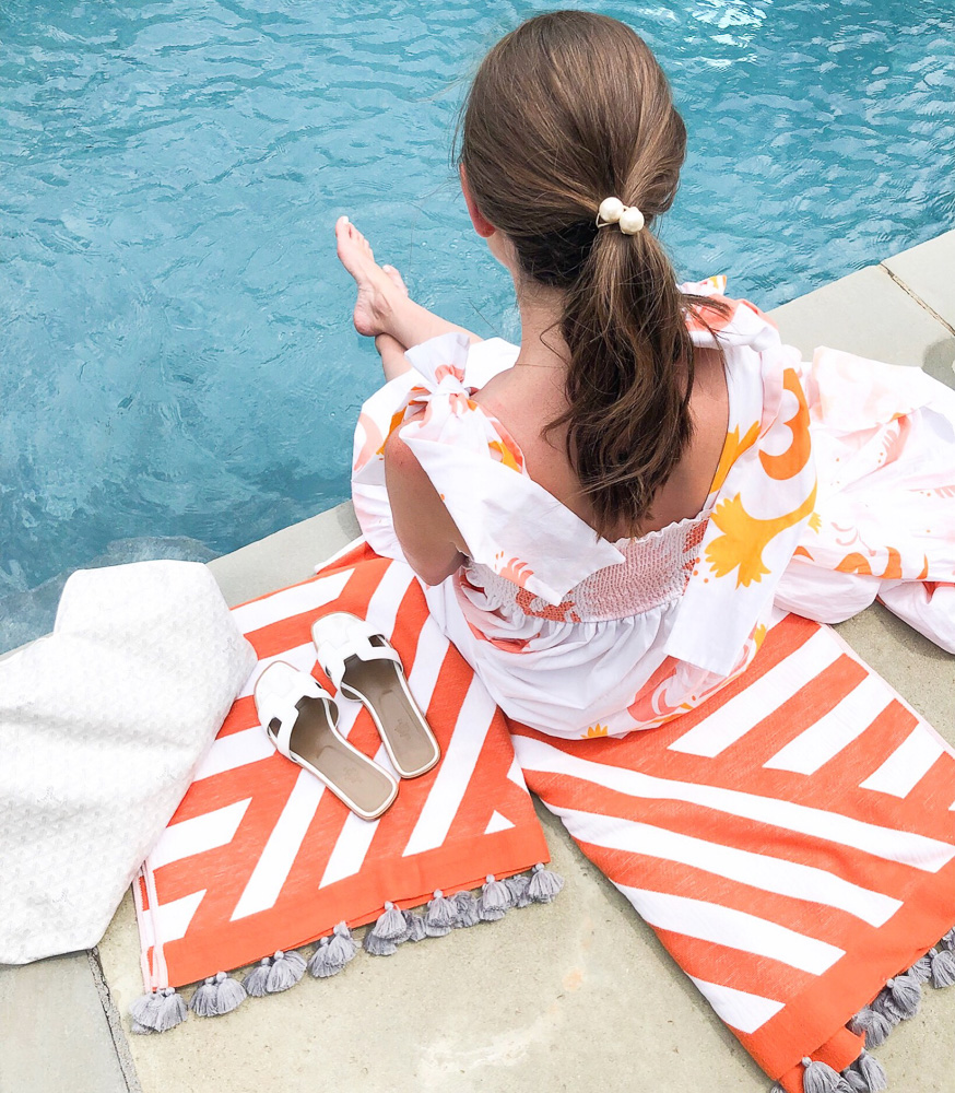 woman sitting by a pool orange white striped tassel towels