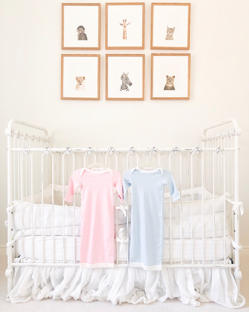 pink and blue newborn nightgowns hanging on crib