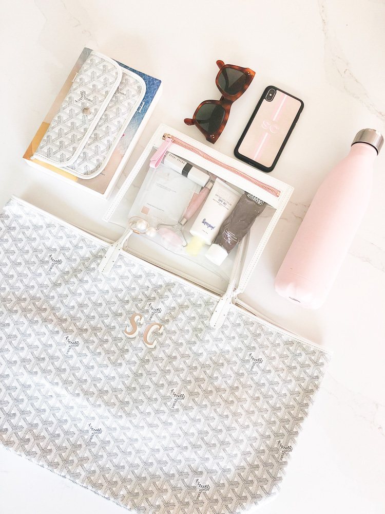 white tote bag matching white pouch clear travel pouch with skincare products iphone sunglasses water bottle