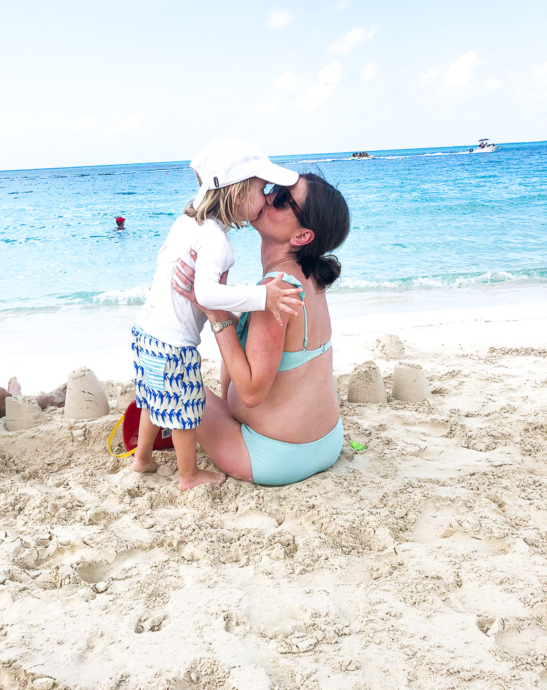 mom and her toddler kissing on beach