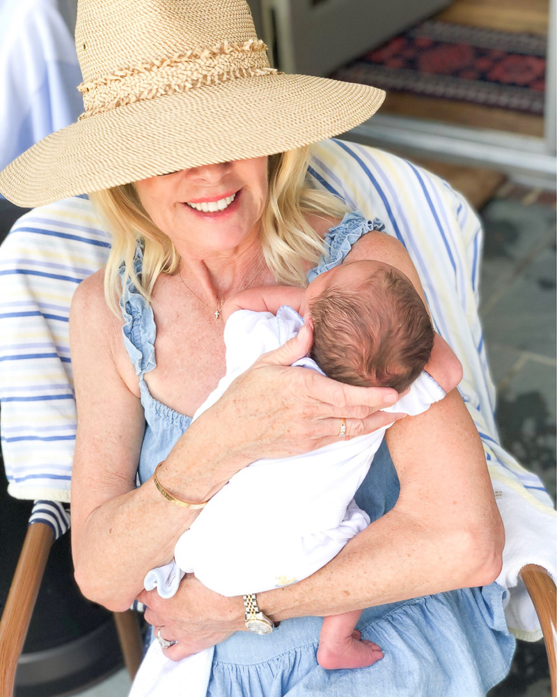 grandmother wearing sun hat holding baby