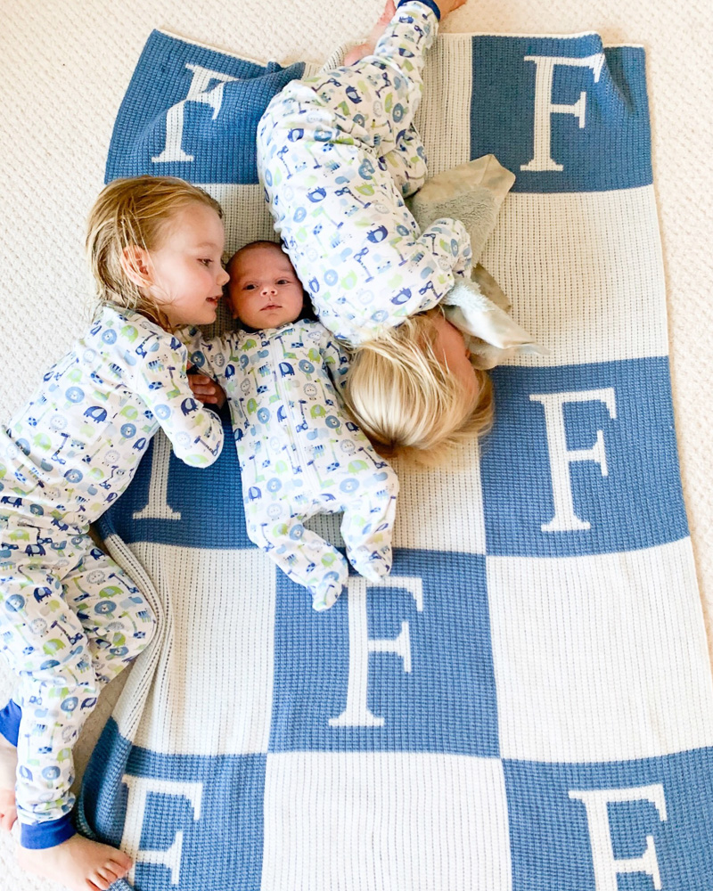 three brothers laying on monogrammed blanket