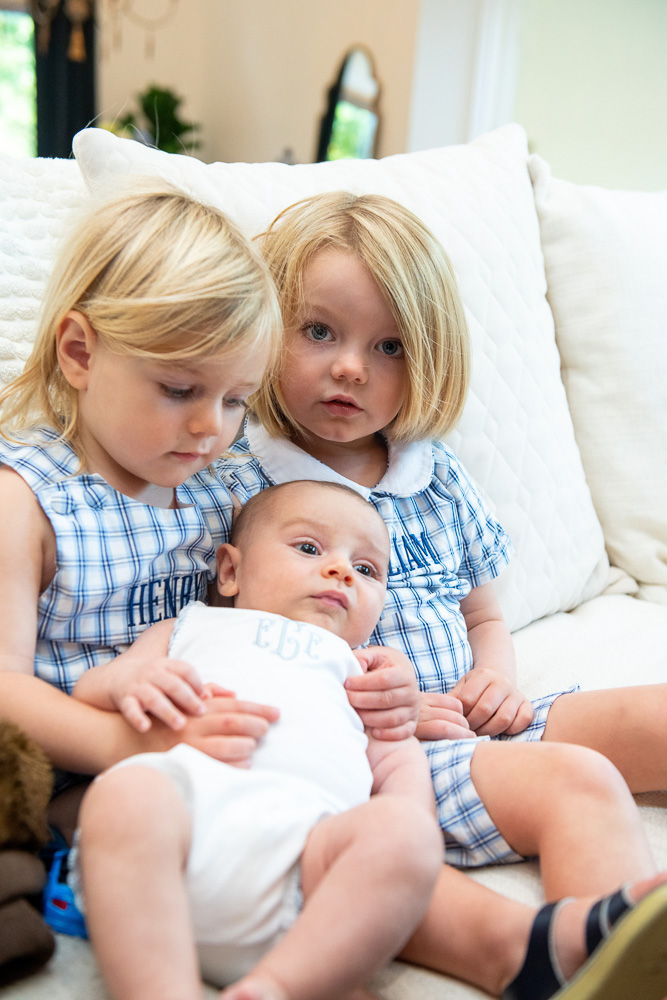 two toddler brothers holding baby