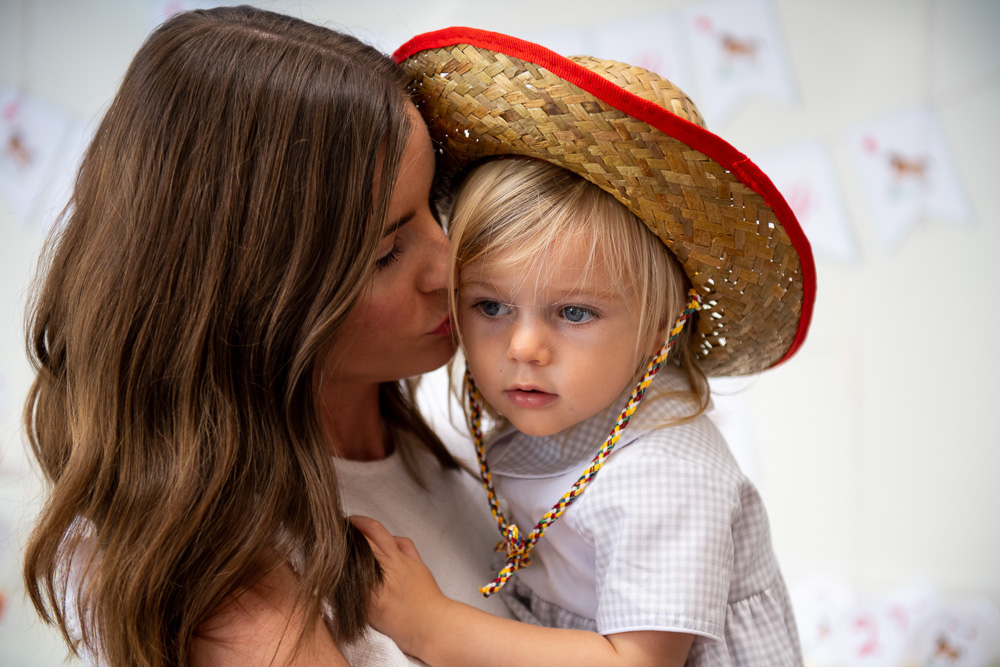 mom kissing toddler boy in cowboy hat