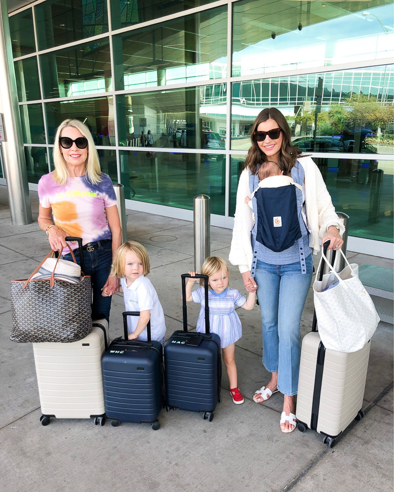 two women at airport with two toddlers and a baby