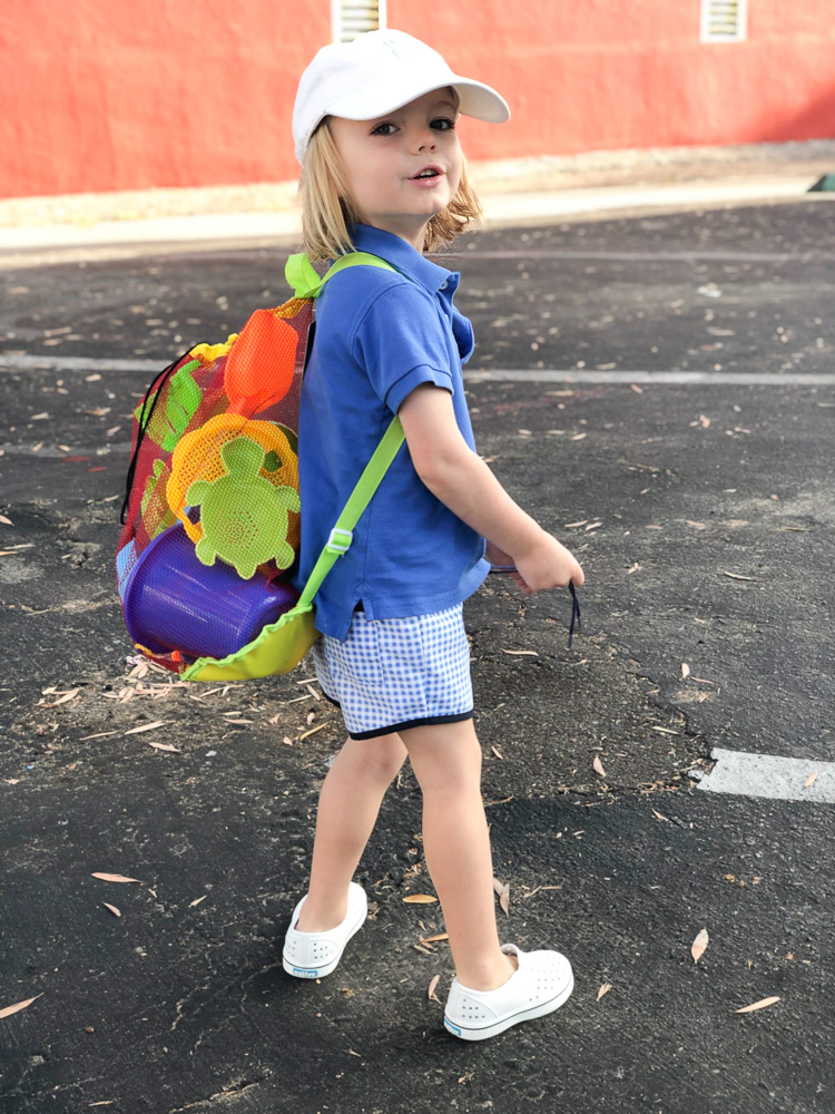 toddler boy carrying backpack of beach toys