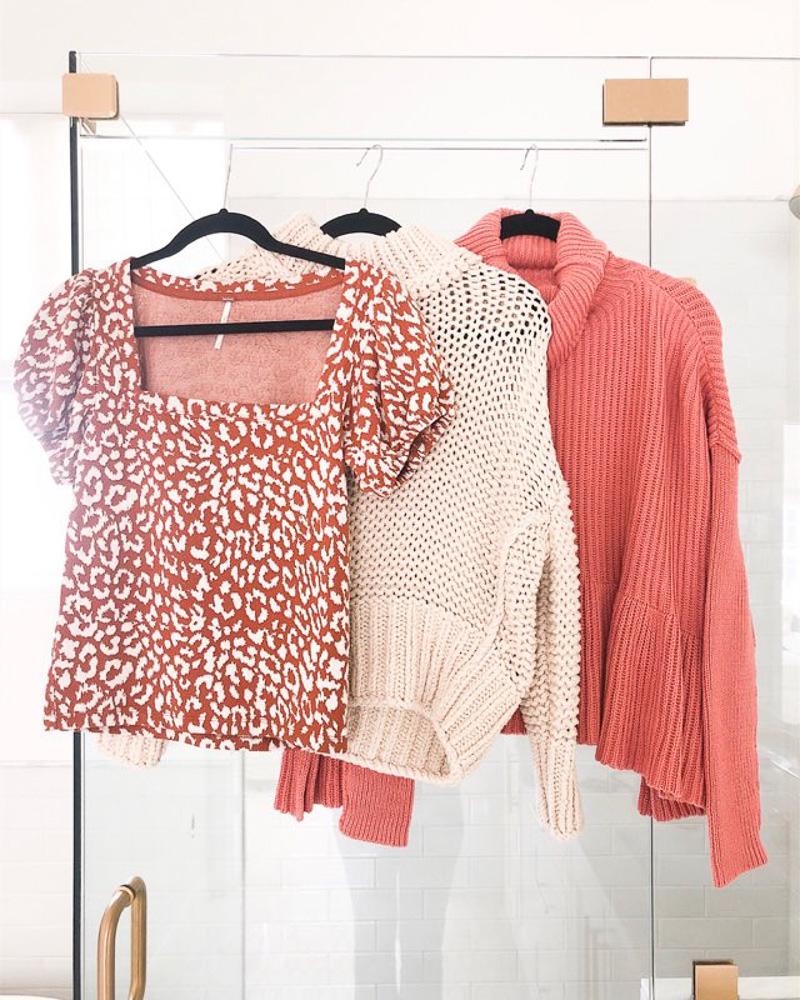 three sweaters hanging