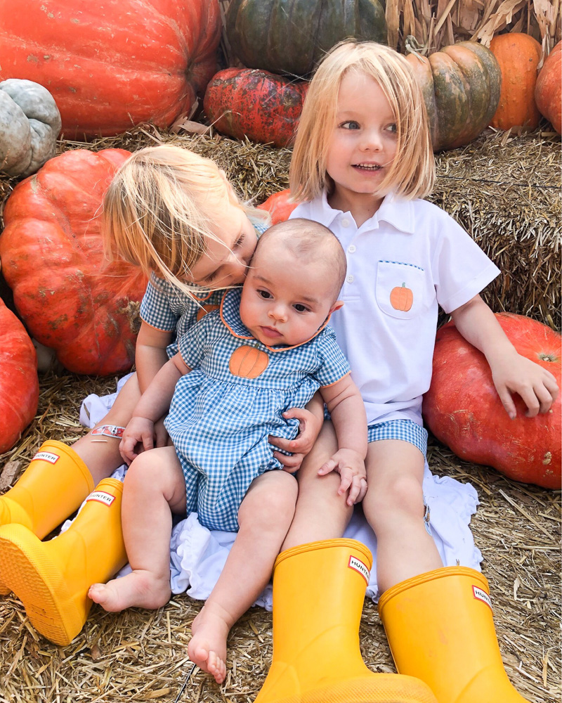two toddlers with baby brother at pumpkin patch