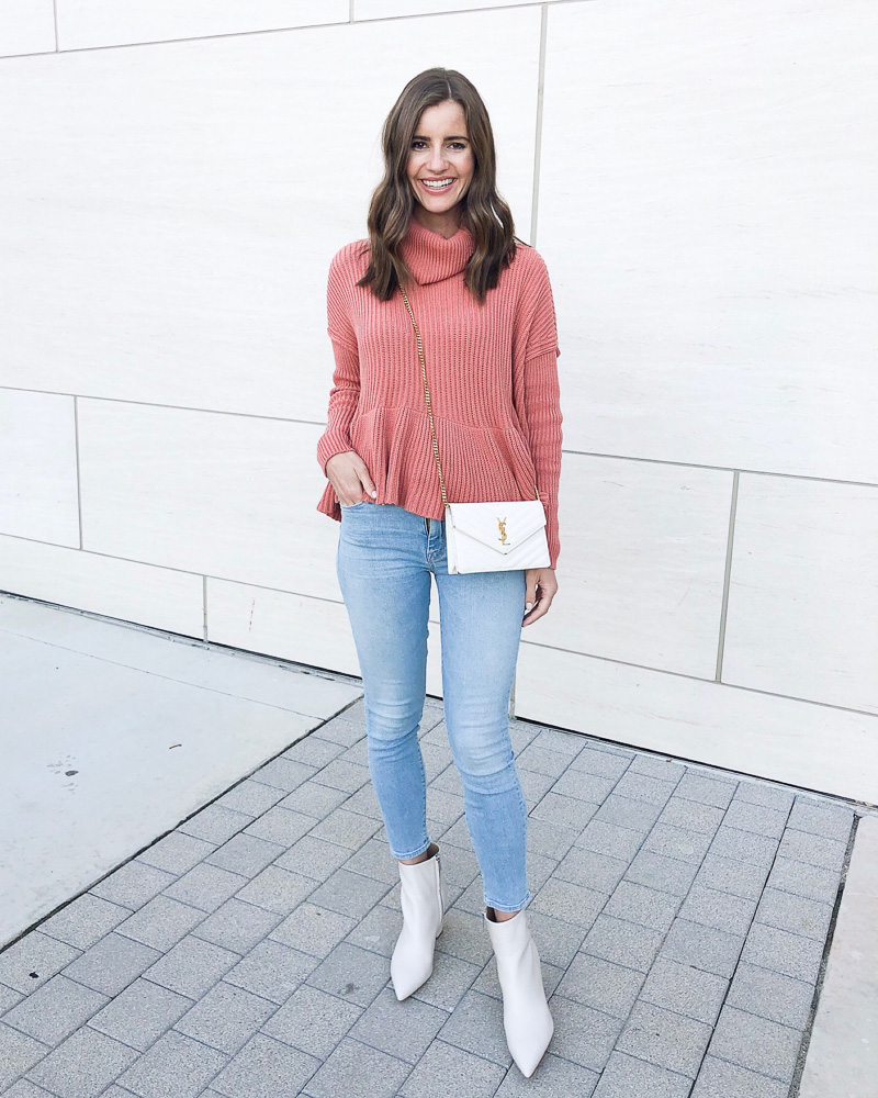 woman in rose colored sweater jeans white boots