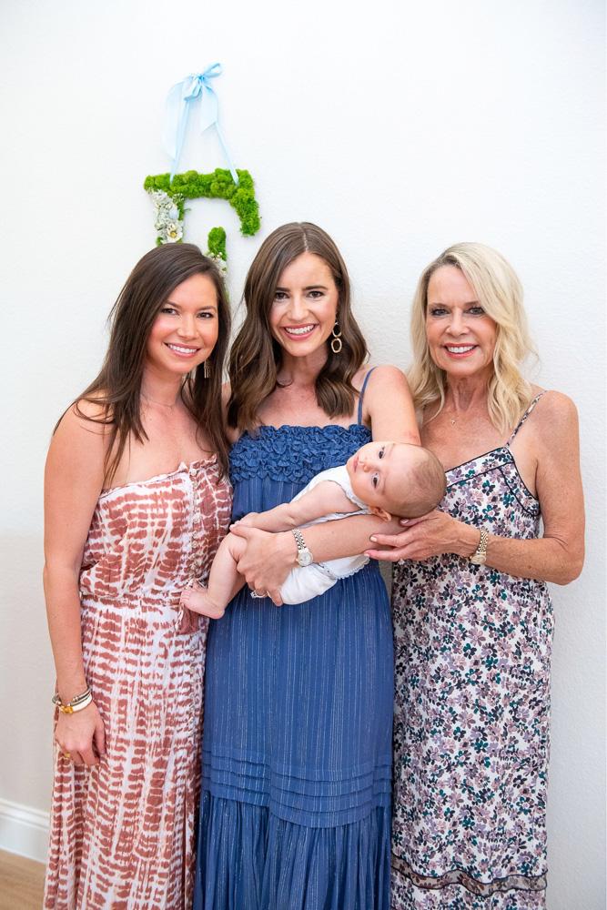 three women holding newborn baby