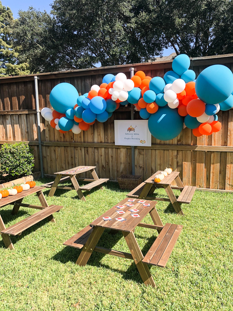 balloons and picnic tables setup for pumpkin party