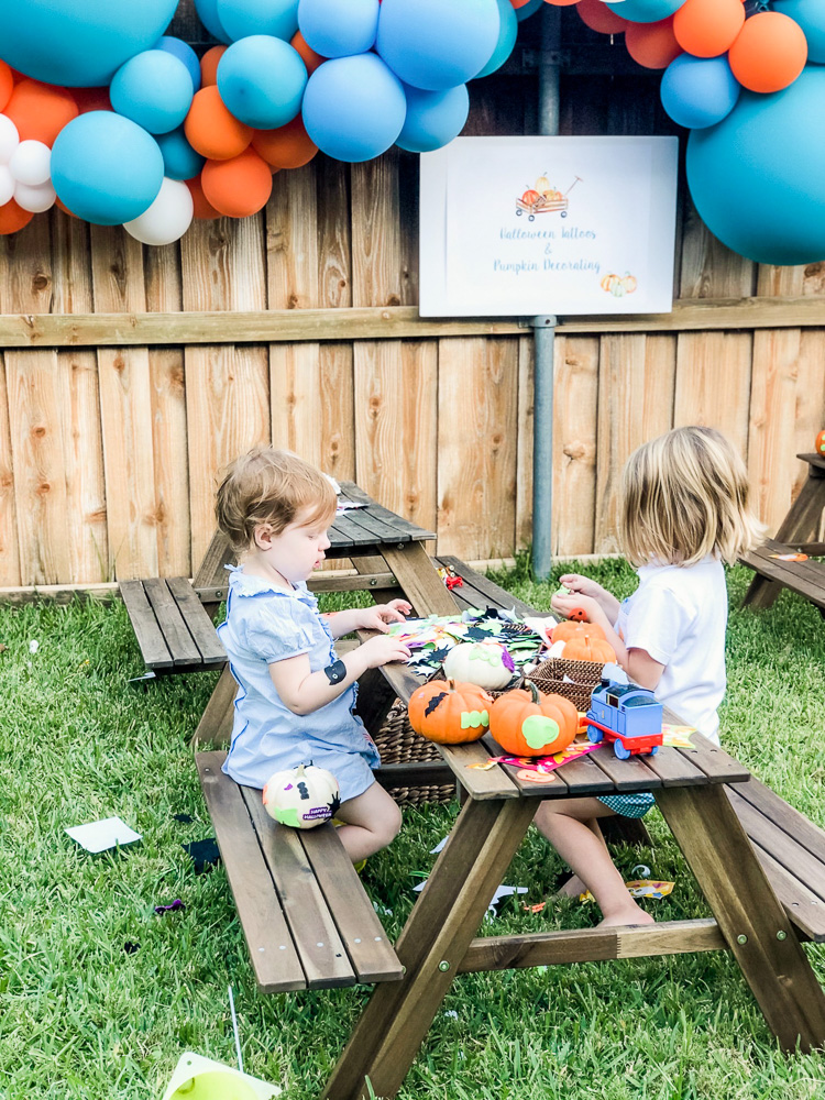 two toddlers decorating pumpkins outside picnic tables