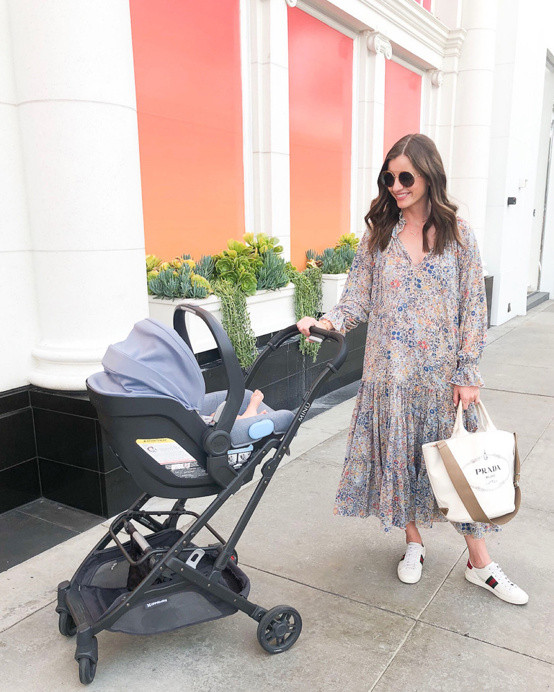 mom pushing baby in stroller outside of louis vuitton exhibit