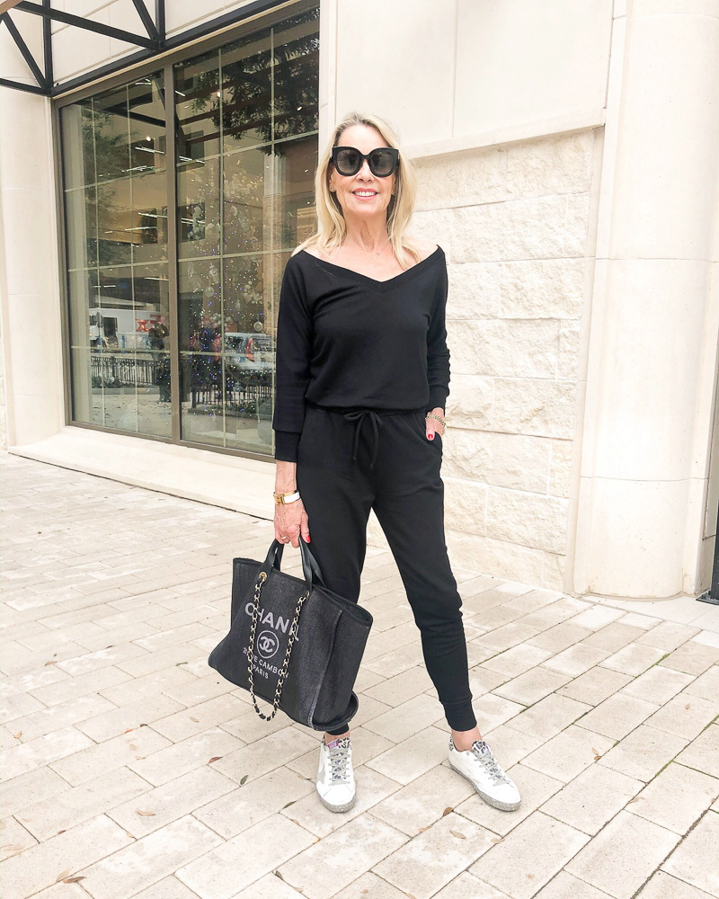 woman wearing black long sleeve jumpsuit sneakers and tote bag