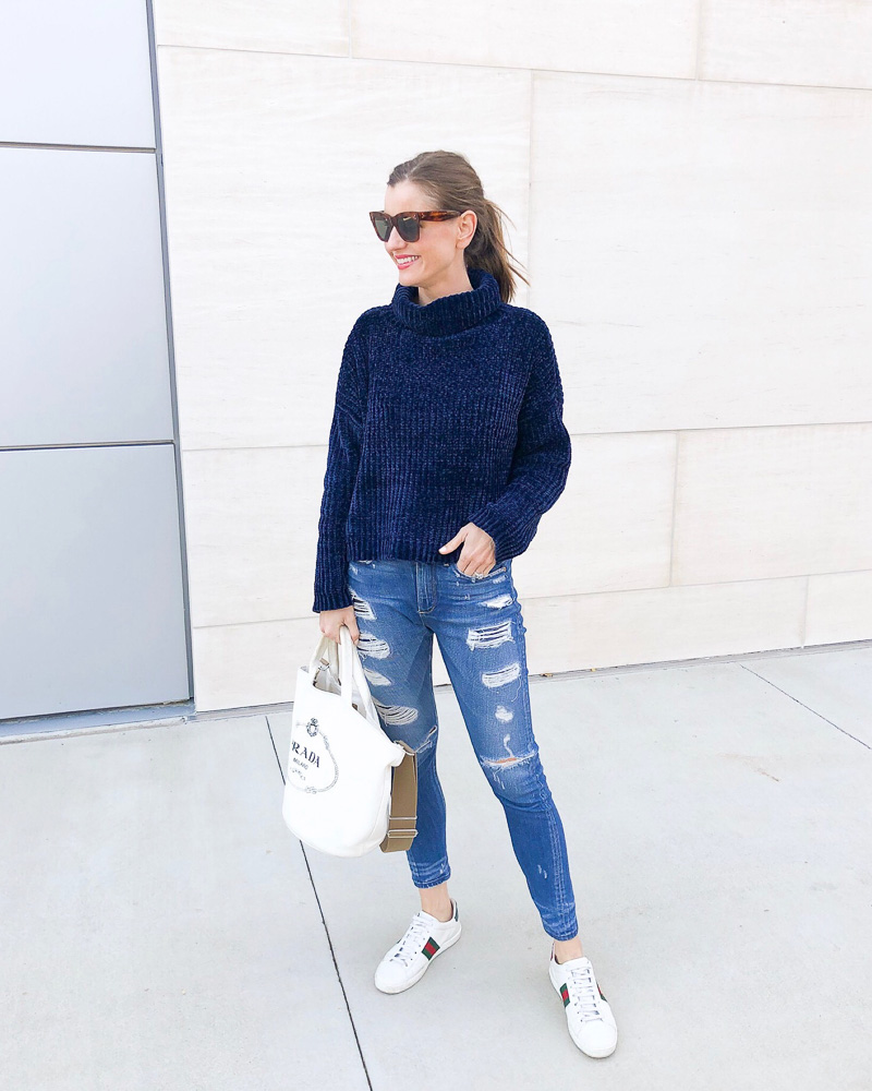 woman in blue sweater and distressed jeans