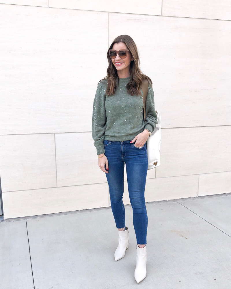 woman in green sweater jeans white booties