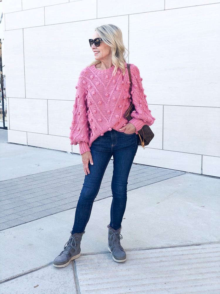 woman wearing pink pom pom sweater skinny jeans and boots