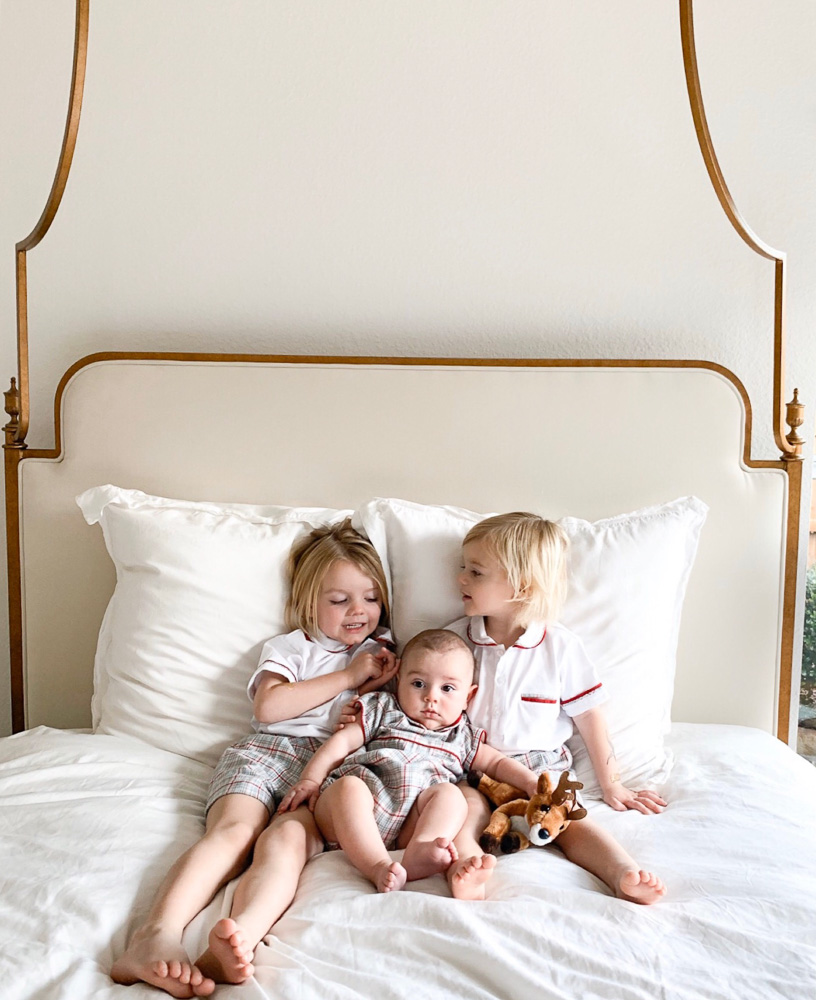 two toddler boys in bed with baby brother