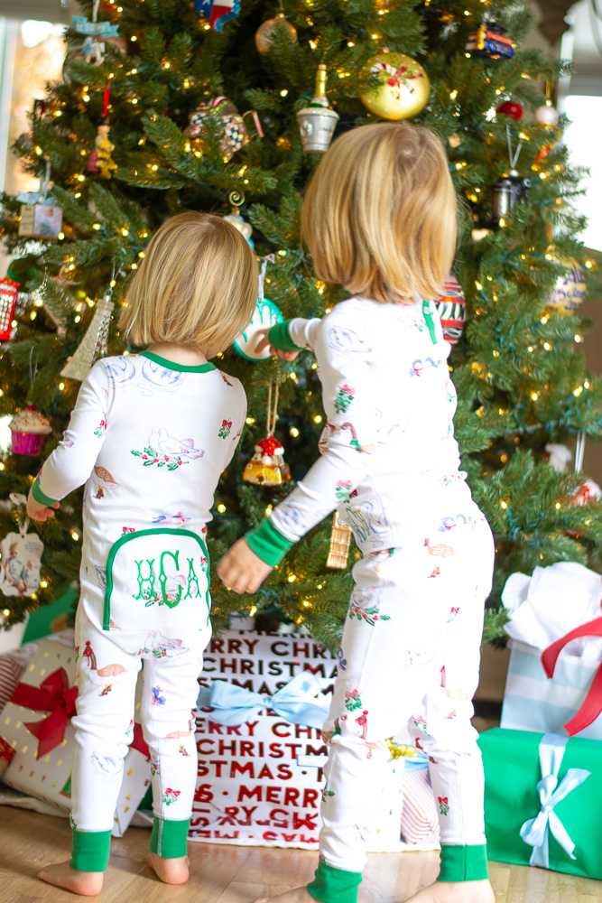 toddler boys by christmas tree in matching pajamas