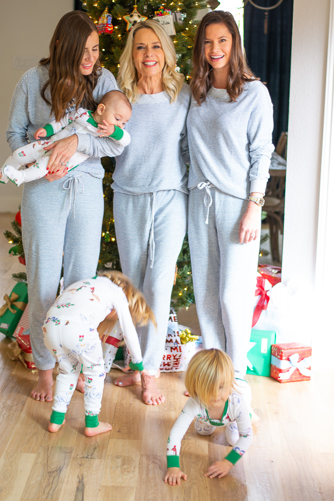family laughing in matching christmas pajamas