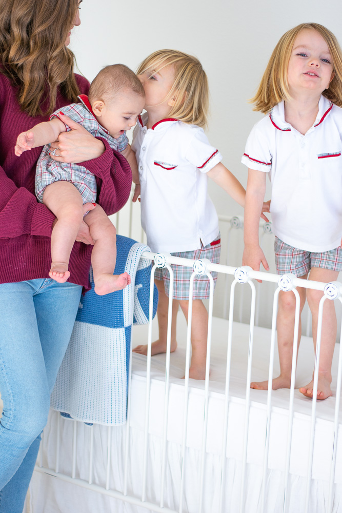 baby and two toddlers in crib