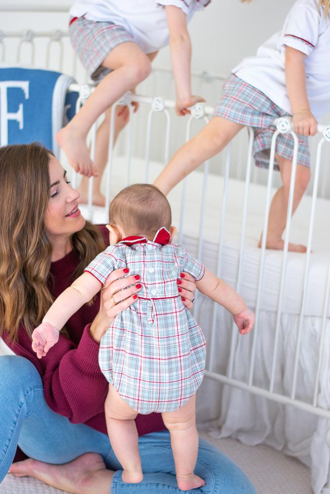 mom watching boys climb into crib