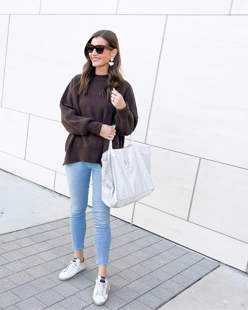 woman wearing brown oversized sweater jeans golden goose sneakers