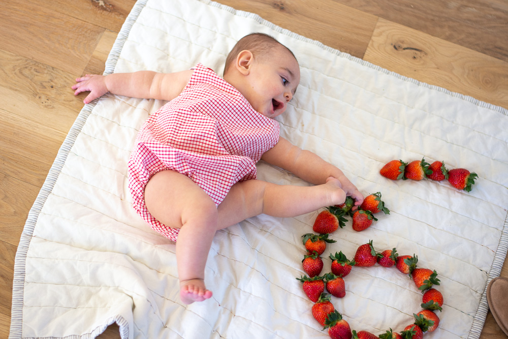 six month old baby next to strawberry six