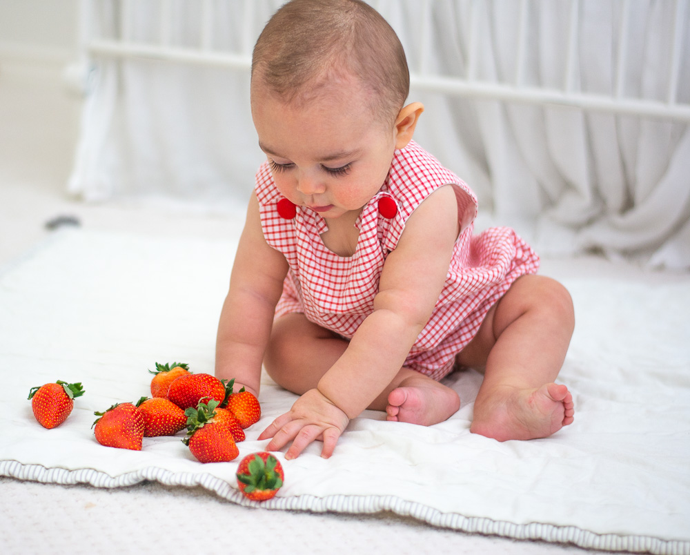 six month old baby with strawberries