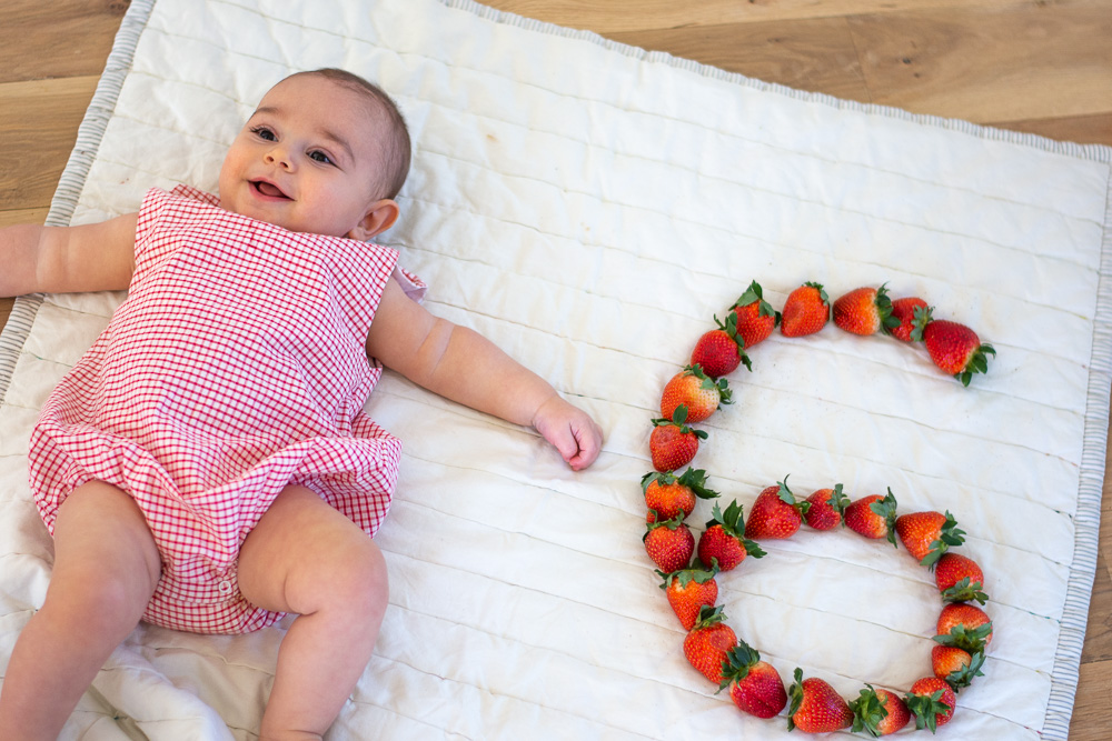 six month old baby next to a strawberry six