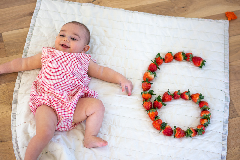 six month old baby next to a six made of strawberries