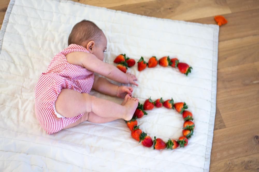 six month old baby laying next to strawberry six