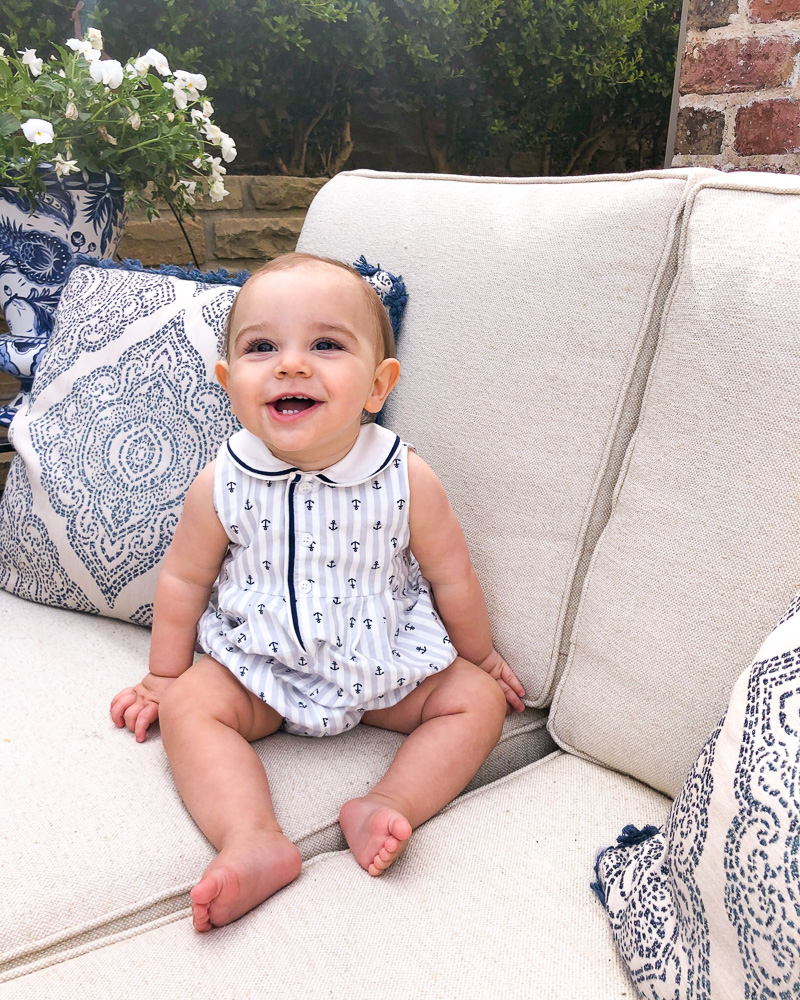 baby laughing sitting outside on settee